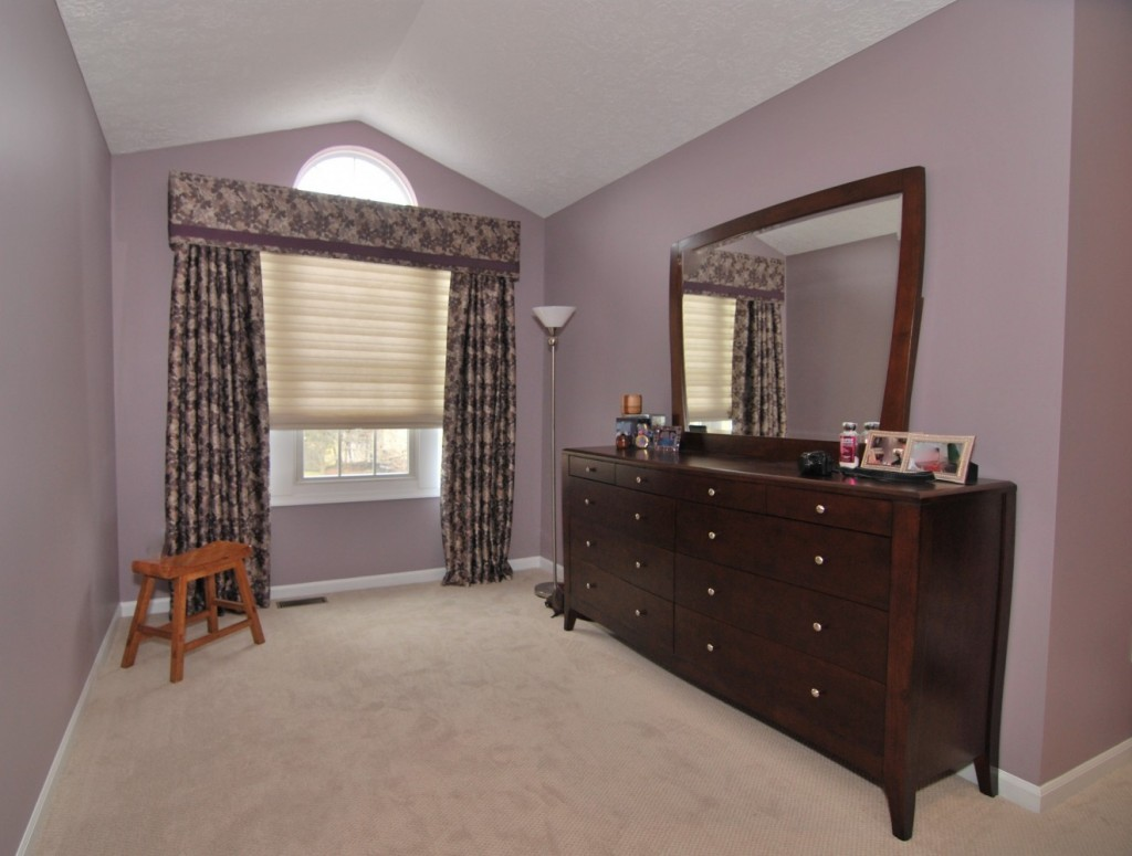 Transitional plum and beige floral custom cornice with drapes and Hunter Douglas Solera shade
