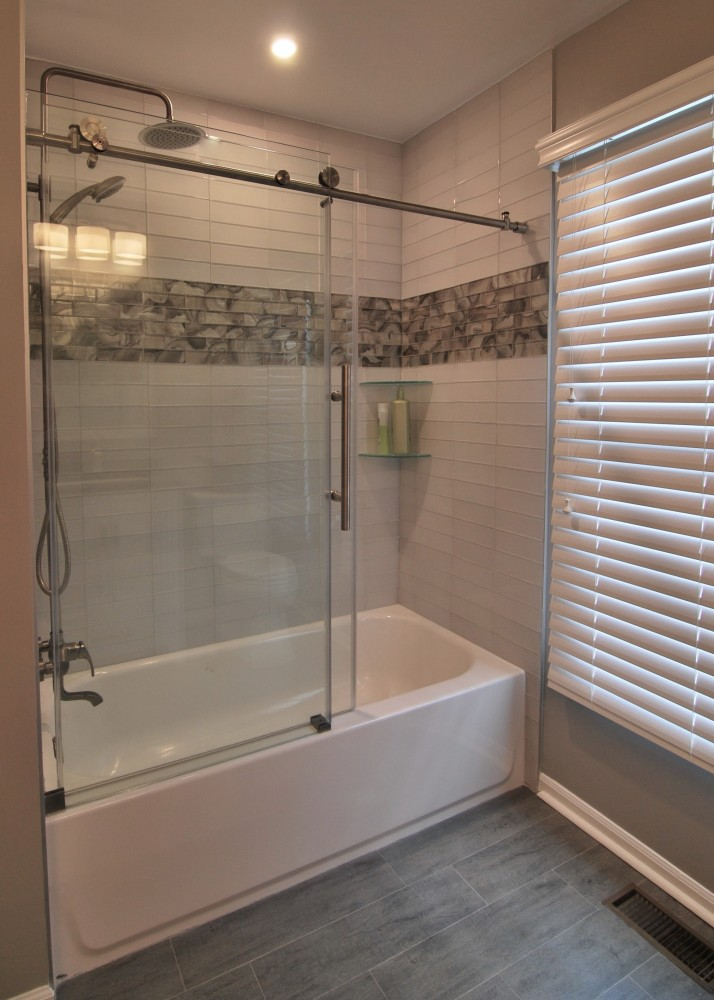 White glass stacked subway tile with grey marbled accent inset and Dreamline Enigma shower doors