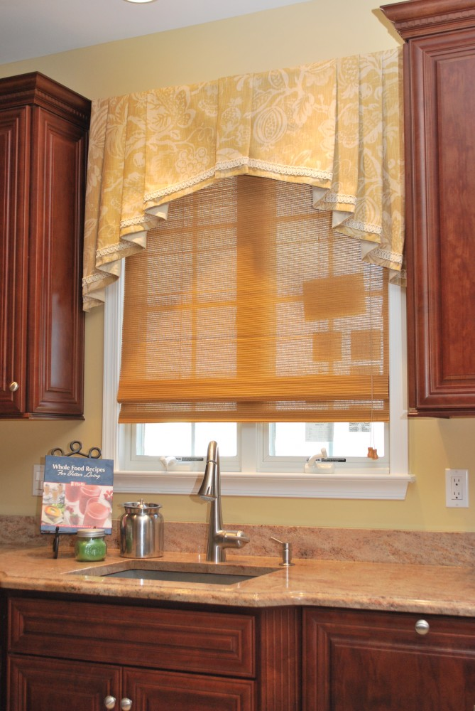 Shaped bottom pleated valance over woven wood Roman shade