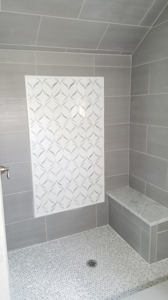 Gray and whitte penny tile and arabesque shower before glass