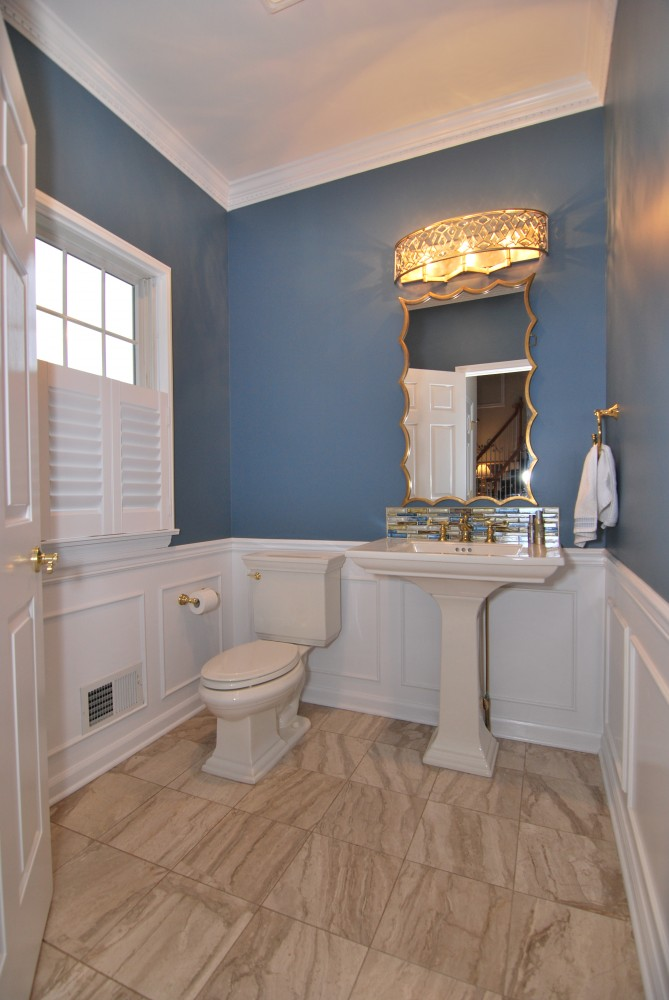 Powder room with marble floors, wainscoating blue walls gold accents