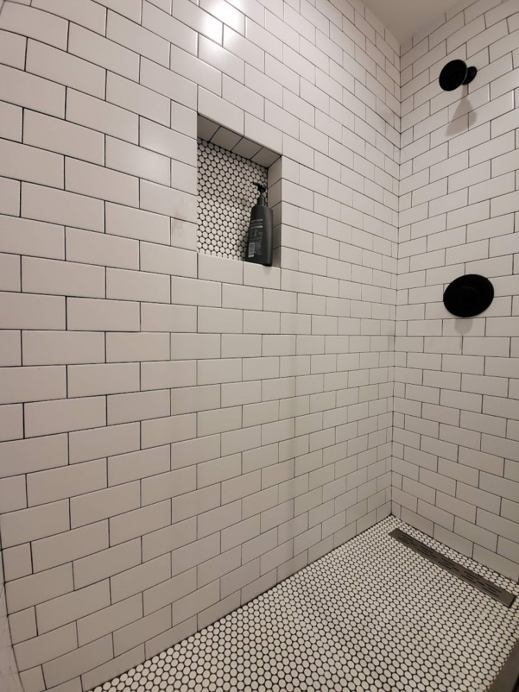 White subway tile, penny tile shower floor, black grout