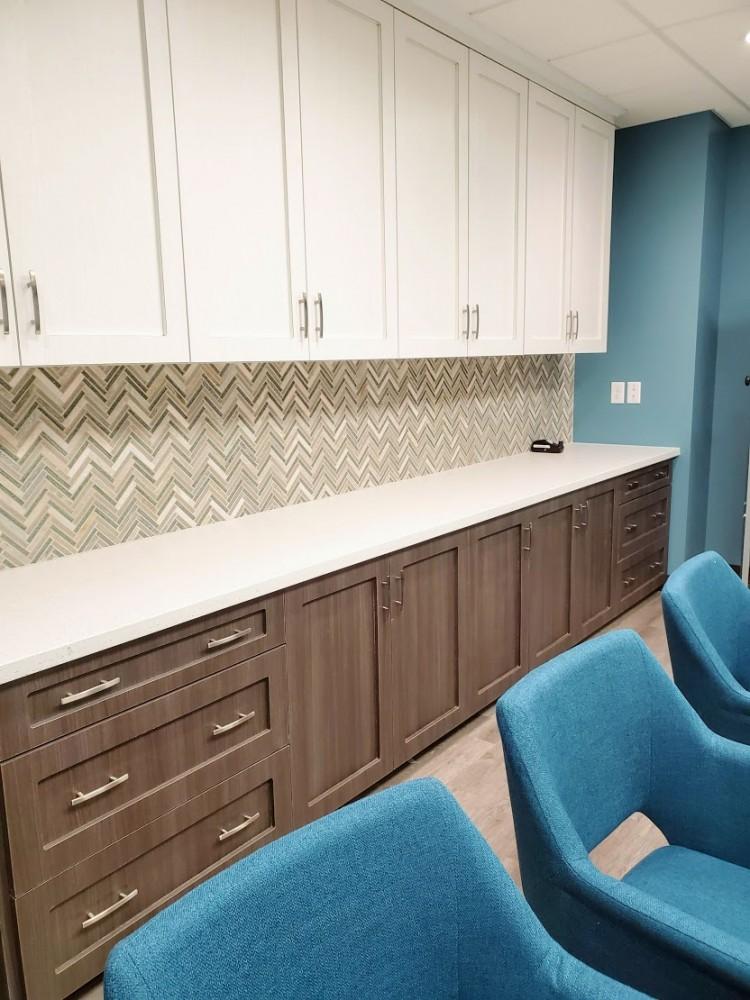 White laminated upper cabinets over herringbone backsplash and grey wood base cabinets