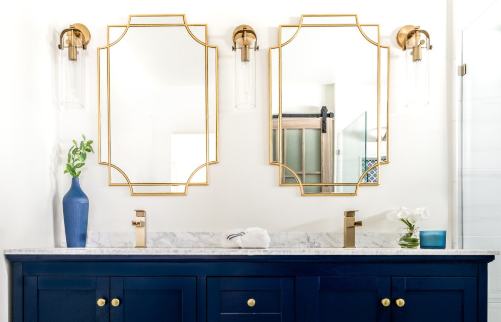 Carrara topped navy double vanity with matt gold mirrors and fixtures